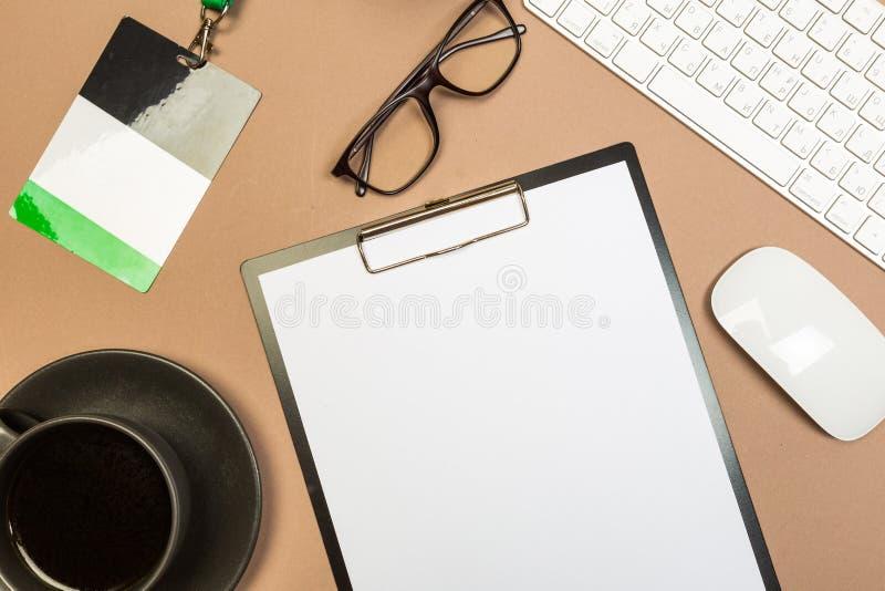 与剪贴板键盘玻璃多汁徽章和咖啡杯的办公桌桌 模板的嘲笑 顶视图 免版税库存照片