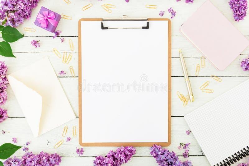 与剪贴板、信封、丁香和辅助部件的Minimalistic工作区在白色背景 自由职业者或博客作者概念 平的la 免版税库存照片