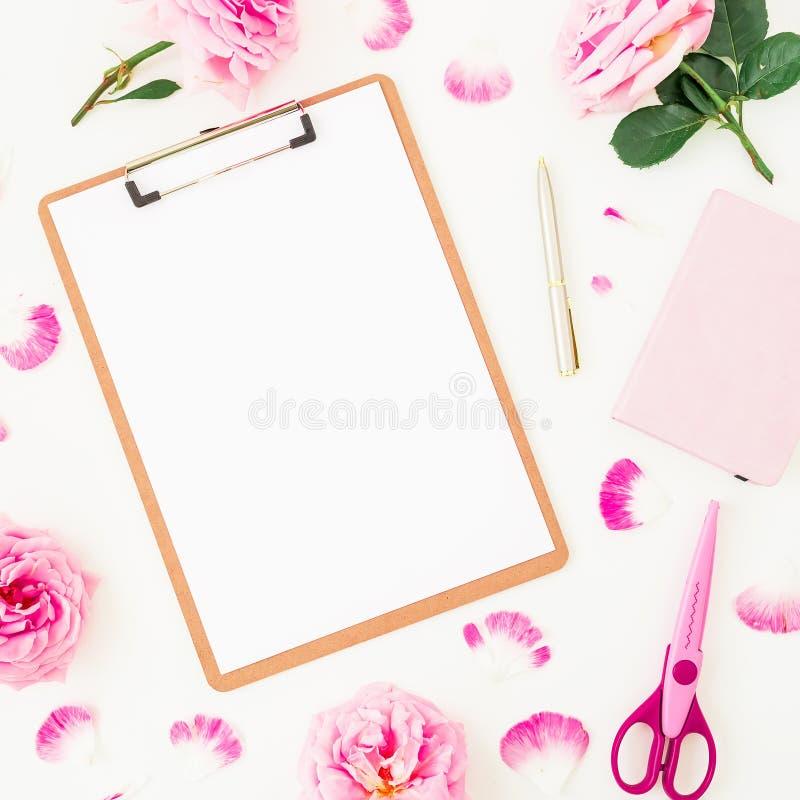 与剪贴板、桃红色玫瑰、瓣和辅助部件的简单派工作区在白色背景 平的位置,顶视图 freela的博客作者 库存照片