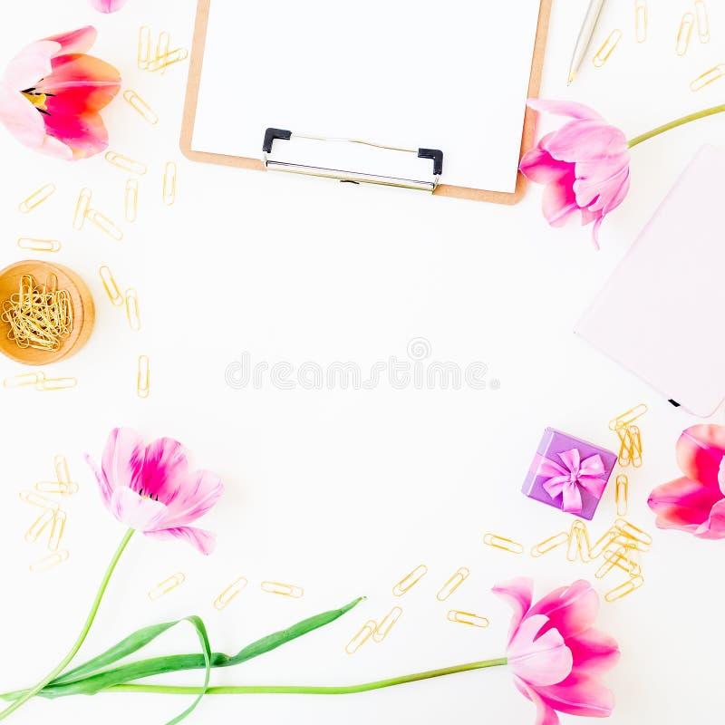 与剪贴板、笔记本、桃红色花和辅助部件的家庭办公室工作区在白色背景 平的位置,顶视图 博客作者或f 免版税图库摄影