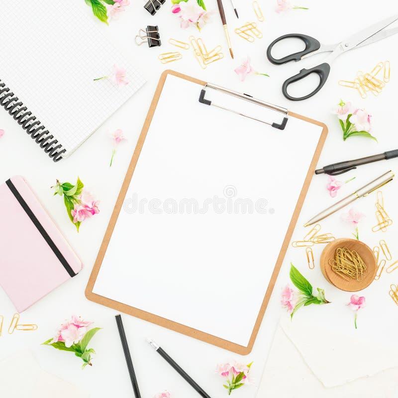 与剪贴板、笔记本、花和辅助部件的博客作者或自由职业者工作区在白色背景 平的位置,顶视图 库存照片