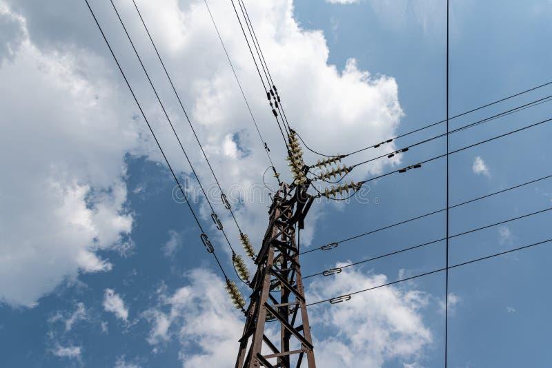 与力量导线的塔反对与蓬松云彩的天空蔚蓝 免版税图库摄影
