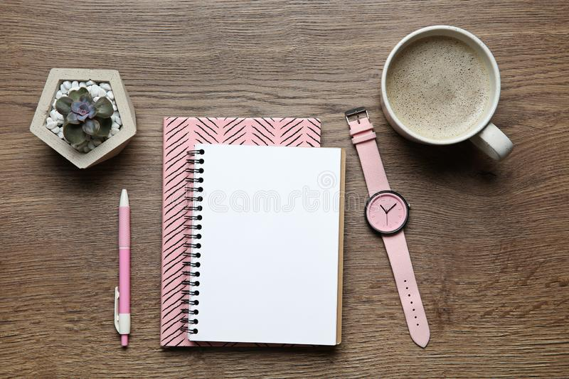 与办公室文具和咖啡的平的被放置的构成在木桌上的 空间为 免版税库存图片