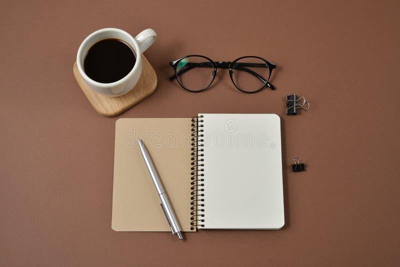 与办公用品、笔、咖啡杯、笔记薄和玻璃的大模型工作区在棕色背景 平的位置,顶视图, 库存图片