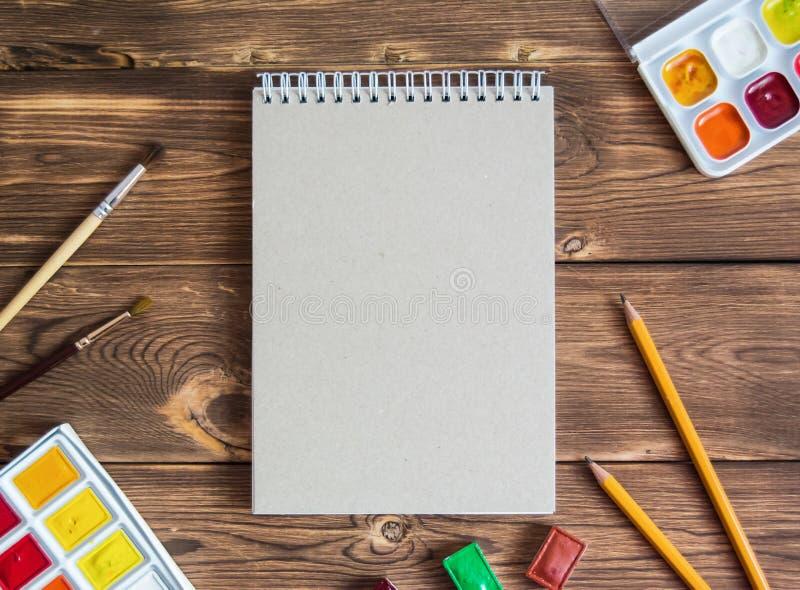 与办公用品的笔记薄在木棕色背景 免版税库存照片