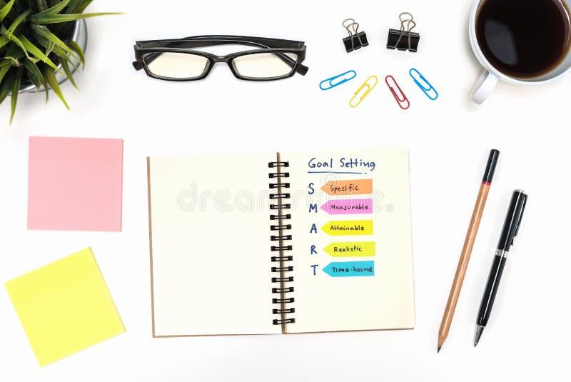 与办公用品的聪明的目标设置在白色书桌 免版税图库摄影