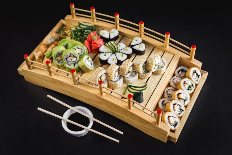 与加利福尼亚、鲕梨、hosomaki和天麸罗卷的寿司桌在一张木桌上 库存照片