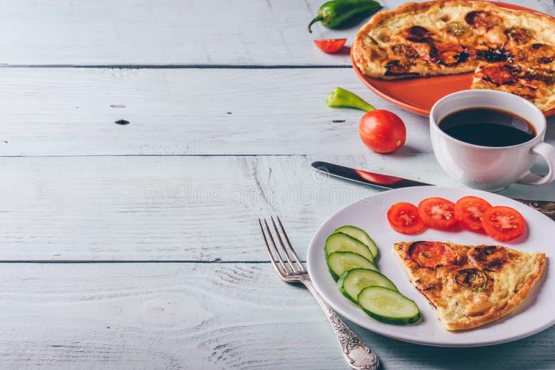 与加调料的口利左香肠、蕃茄和辣椒的菜肉馅煎蛋饼在板材和咖啡 库存图片