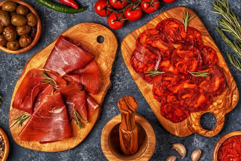 与加调料的口利左香肠, jamon,野餐桌的西班牙塔帕纤维布 免版税库存照片