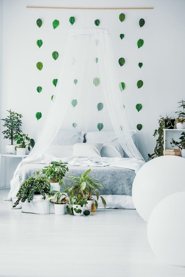 与加长型的床、都市密林和绿色叶子的白色卧室内部在墙壁上 库存图片