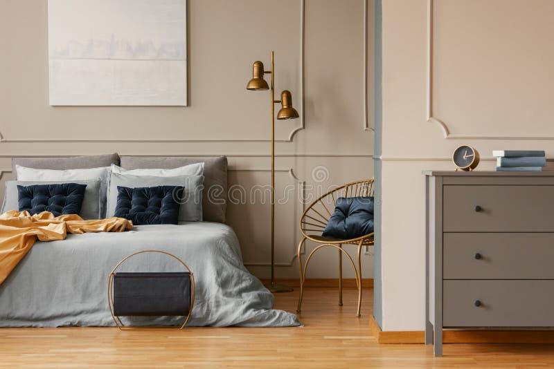 与加长型的床的典雅的卧室内部,绘在墙壁和灰色洗脸台上 免版税库存照片
