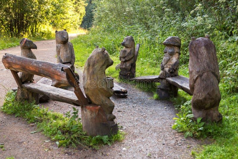与动物木雕塑的长凳在terrenkur健康的沿Belokurikha山河落后 库存照片