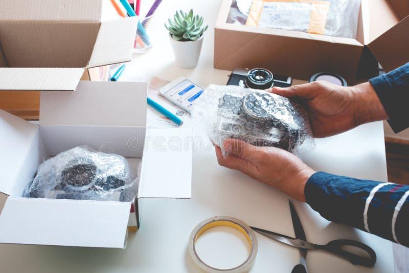 与包裹产品的年轻人的网络购物概念到箱子 电子商务,运输的送货服务 企业零售 免版税库存照片