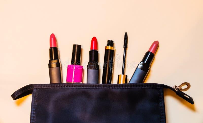 与化妆产品的构成袋子说出对米黄背景 库存图片
