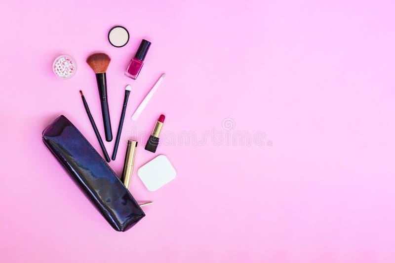 与化妆用品的妇女平的被放置的构成背景 眼影膏,染睫毛油,粉末,唇膏,指甲油,刷子,镊子,海绵和 免版税库存图片