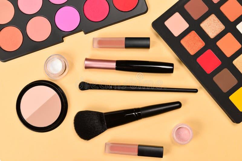 与化妆美容品、眼影、颜料、唇膏、刷子和工具的专业构成产品在灰棕色 免版税库存照片
