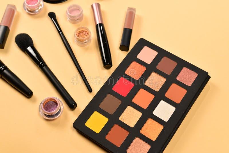 与化妆美容品、眼影、颜料、唇膏、刷子和工具的专业构成产品在灰棕色 图库摄影