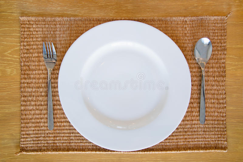 与匙子和叉子集合的白色空的盘 免版税库存图片