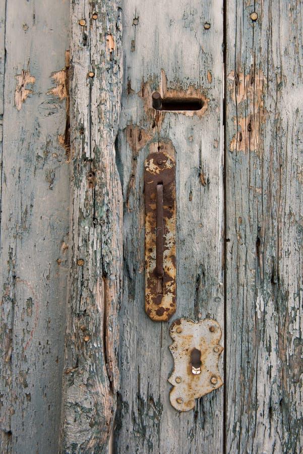 与匙孔的老和生锈的门把手在苍白和葡萄酒蓝色木门 免版税库存图片