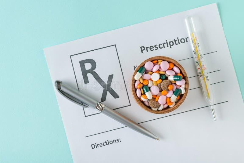 与医生的处方的板料,有药片的木在蓝色背景的碗和注射器 顶视图 免版税图库摄影