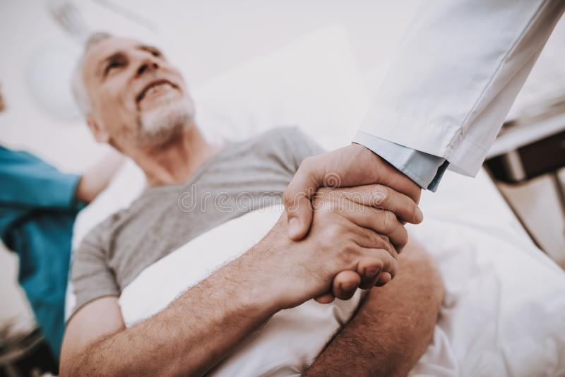 与医生的耐心握手 老人在Clinik 免版税图库摄影