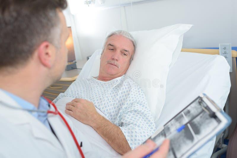 与医生的资深耐心看的X-射线在医院 免版税图库摄影