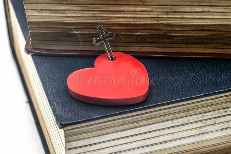与十字架和圣经的红色心脏 图库摄影
