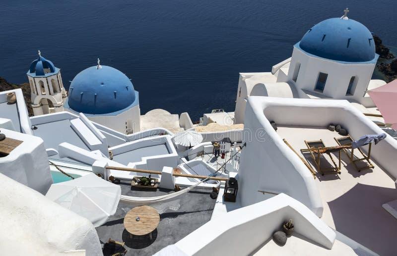 与十字架的传统希腊白色教会曲拱和响铃在村庄基克拉泽斯海岛圣托里尼希腊Oia  免版税库存照片