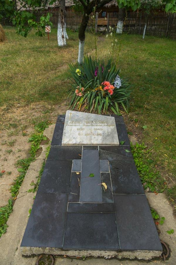 与十字架的纪念石平板在绿草和花床背景与花的 库存图片