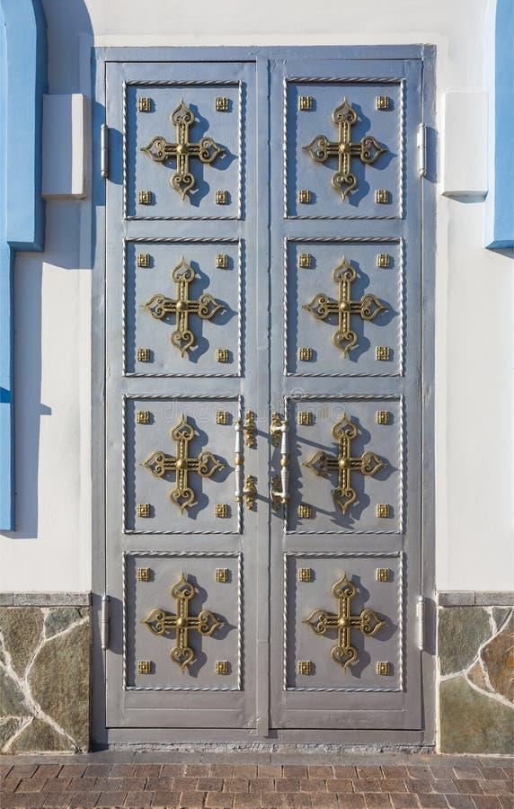 与十字架的轻的金属门 免版税库存照片
