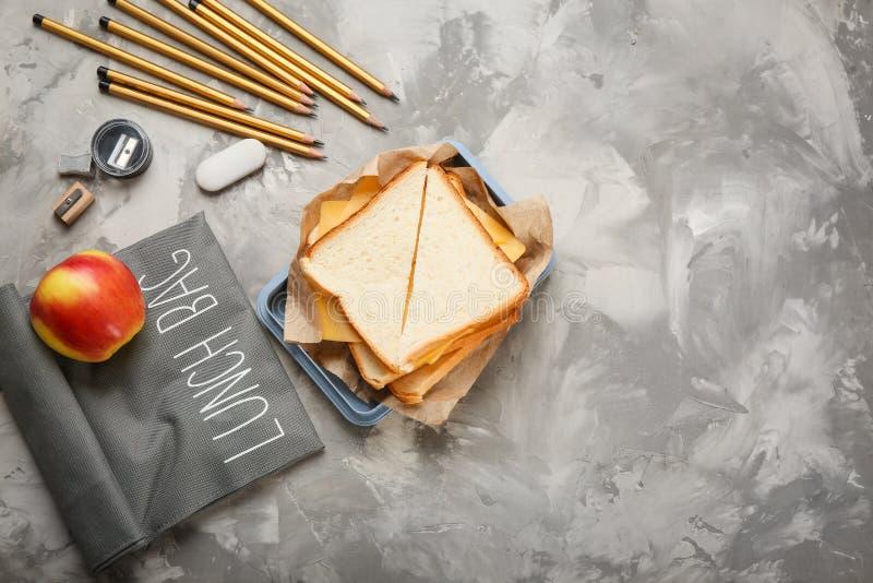 与午餐盒,鲜美三明治的平的位置构成 免版税库存图片