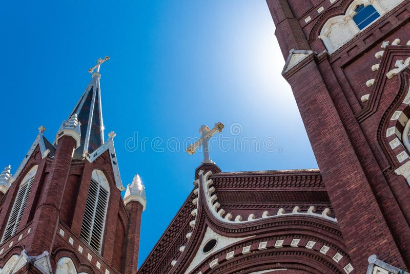 与华丽哥特式复兴建筑学教会,与太阳焕发的天空蔚蓝的由后照的白色十字架 免版税库存图片