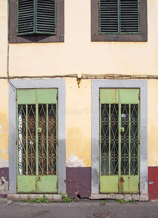 与华丽栅格结构的生锈的绿色金属门在一家遗弃被放弃的商店的前面有退色的黄色和红色墙壁的和 库存照片