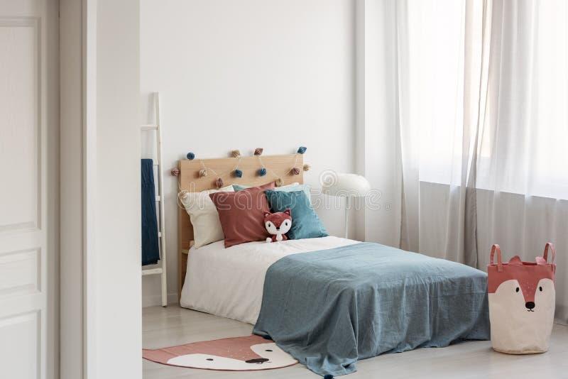 与单人床的明亮的卧室内部与在白色卧具的绿松石毯子和五颜六色的枕头和玩具 库存图片