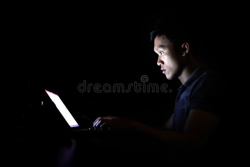 与单独膝上型计算机的年轻程序员学生奔跑任务在午夜在暗室 免版税库存图片