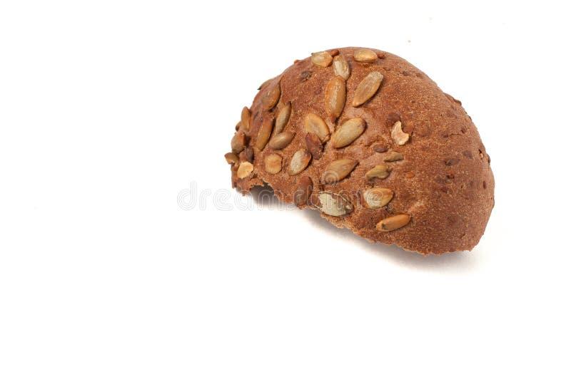 围绕与南瓜籽的一个小圆面包,在白色背景被隔绝 免版税库存照片
