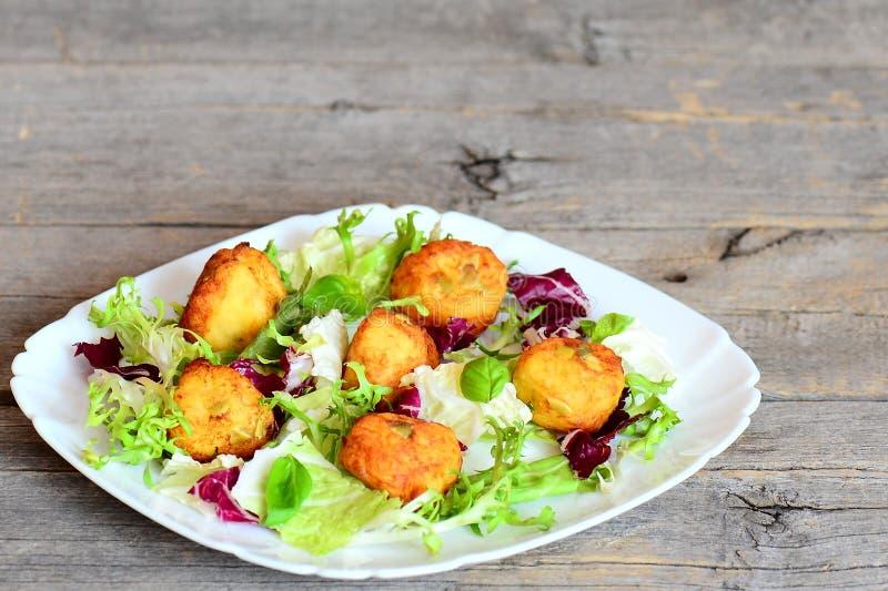 与南瓜籽的金黄油煎的土豆泥炸肉排服务与新鲜的莴苣混合和蓬蒿在板材 库存图片