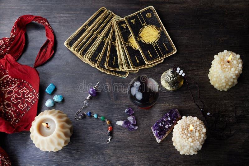 与占卜用的纸牌、不可思议的石头和蜡烛的静物画在木桌上 算命集会或不可思议的仪式 免版税库存图片