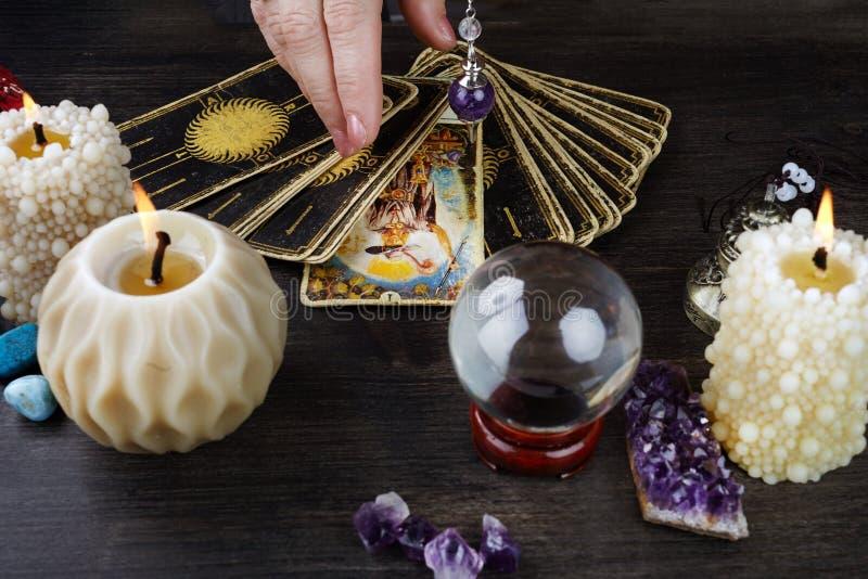 与占卜用的纸牌、不可思议的石头和蜡烛的静物画在木桌上 算命集会或不可思议的仪式 库存照片