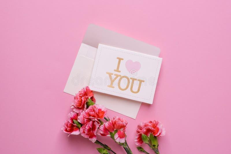 与卡片的一个信封我爱你和在桃红色背景的桃红色花 库存照片