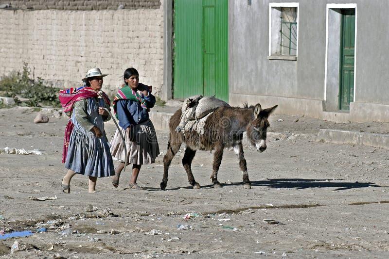 与印地安妇女和驴,玻利维亚的街道视图 免版税库存图片
