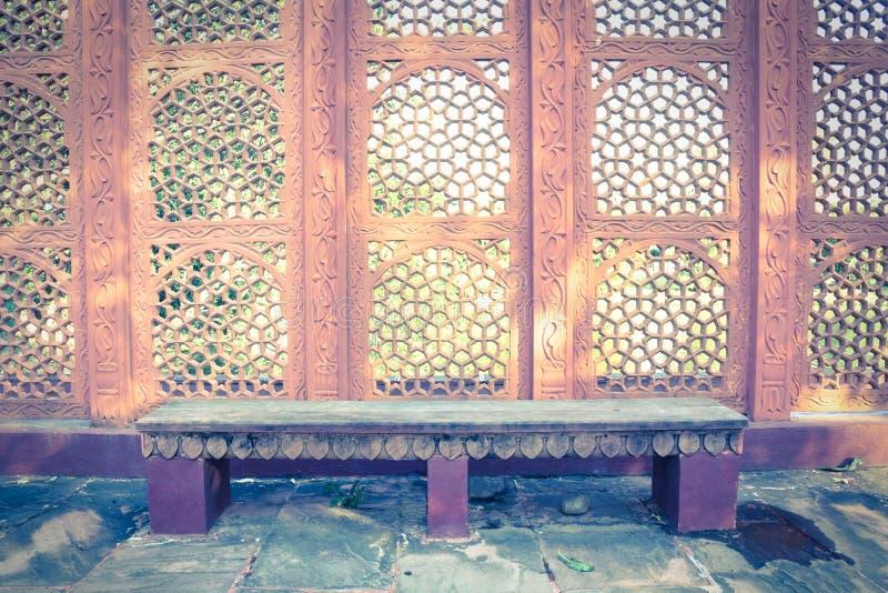 与印地安样式墙壁的石长凳。 免版税图库摄影