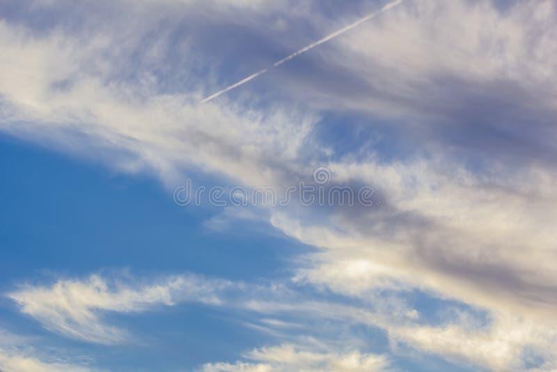与卷云和转换轨迹的天空蔚蓝在日落 免版税库存图片