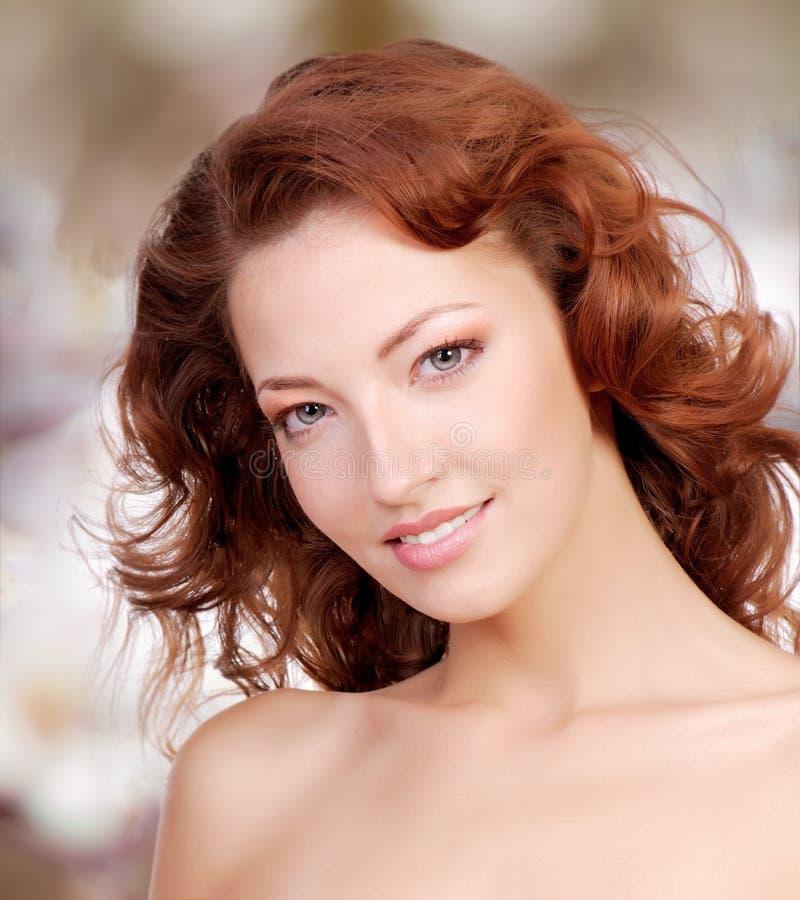 与卷发的美丽的妇女面孔 免版税库存图片