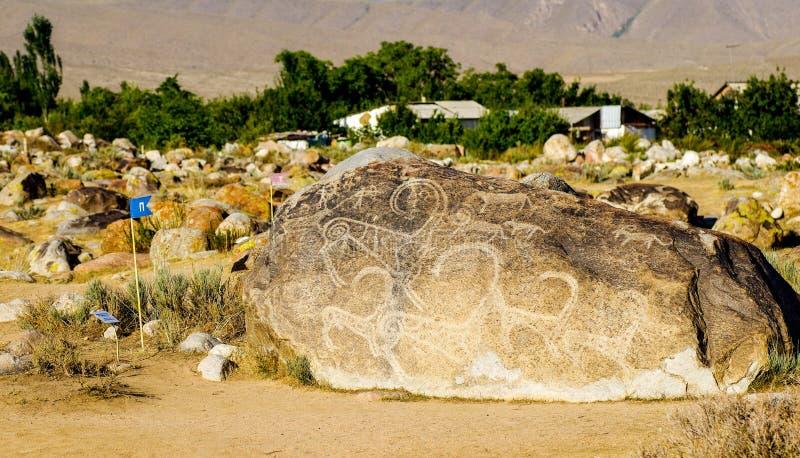 与历史刻在岩石上的文字的古老雕刻在吉尔吉斯斯坦 库存照片