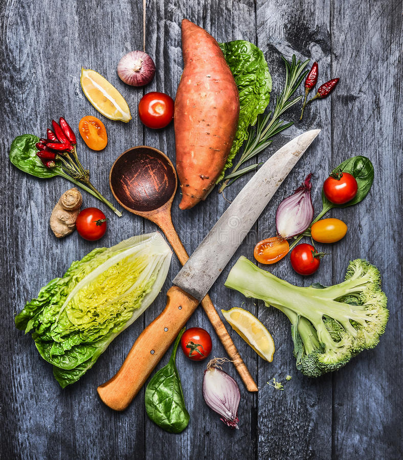 与厨刀和选择木匙子的未加工的有机菜 健康烹调的成份在土气木背景 库存照片