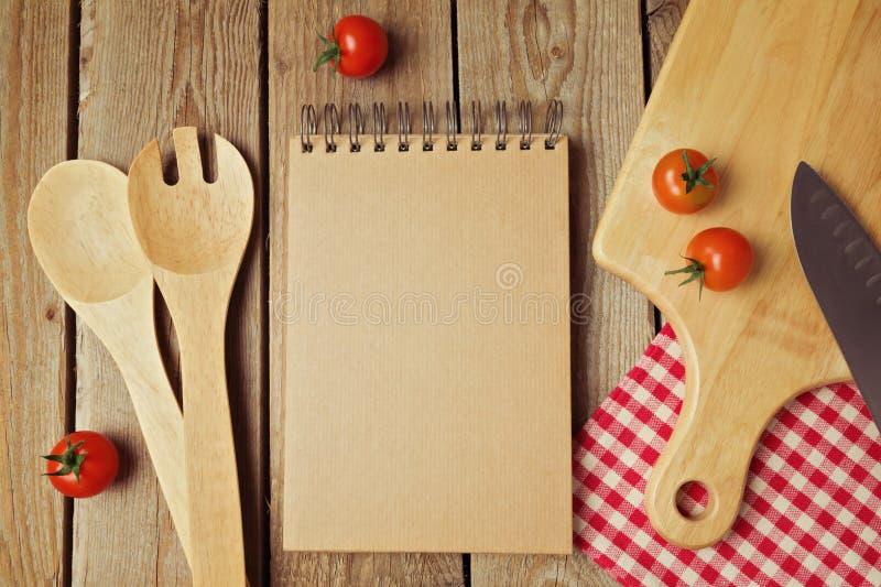 与厨房器物的纸板笔记薄在木桌上 在视图之上 库存图片