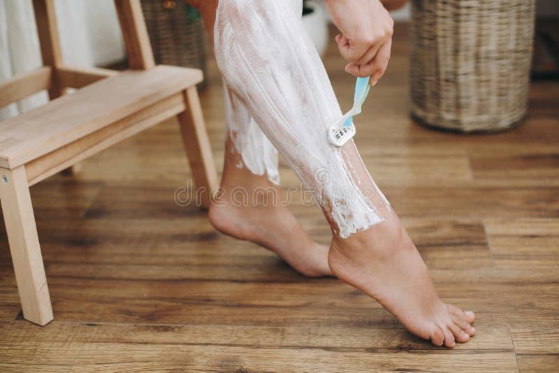 与去壳奶油概念的头发撤除 应用在她的腿的剃须膏和拿着塑料的白色毛巾的年轻女人 图库摄影