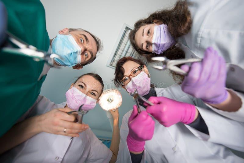 与去膜剂的专业牙齿队在牙齿办公室 牙科 库存照片