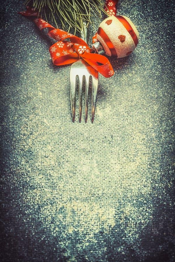 与叉子和红色欢乐假日装饰,顶视图的黑暗的圣诞节食物背景 免版税库存图片